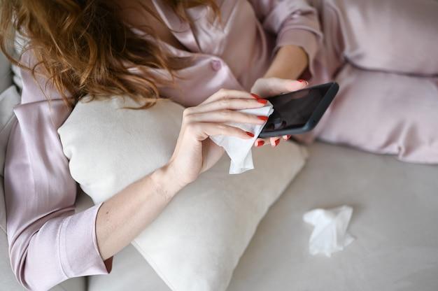 Irriconoscibile donna in pigiama rosa che pulisce il telefono con un disinfettante per le mani, usando un batuffolo di cotone con alcool per pulire per evitare di contaminare con il virus corona. pulizia smartphone per eliminare i germi, covid-19.