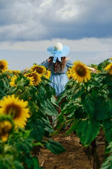 Donna irriconoscibile che attraversa il campo di girasoli allargando le mani ai lati. giovane donna in abito blu che mostra emozioni gioiose.