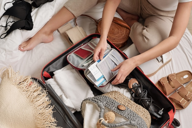 Irriconoscibile donna seduta sul letto tra roba estiva e smistamento documenti di turisti