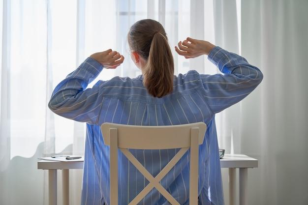 Donna irriconoscibile che si allunga dopo lunghe ore di lavoro da casa con difficoltà di lavoro a distanza