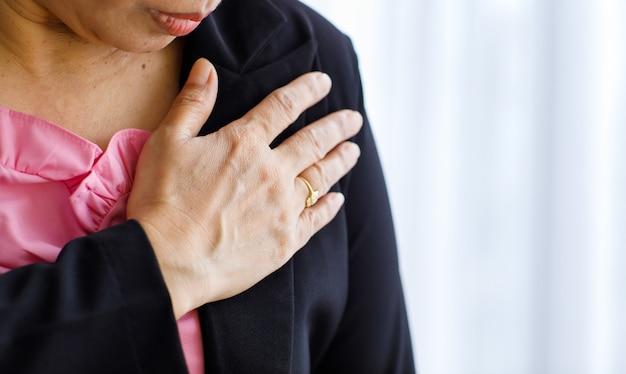 Donna irriconoscibile che soffre di infarto improvviso e tiene il petto. concetto di assistenza sanitaria di emergenza e affetto da insufficienza congestizia o rianimazione cardiopolmonare, problema cardiaco.