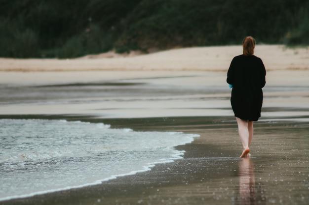 Donna irriconoscibile che cammina sulla spiaggia sabbiosa in una giornata nuvolosa