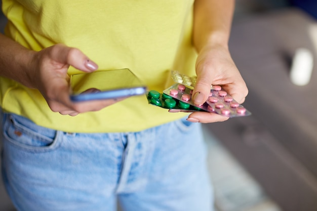 Donna irriconoscibile con blister di pillole e smartphone in mano utilizzando il negozio di farmacia online