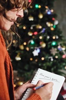 Una donna irriconoscibile con un maglione arancione tiene un quaderno con le parole obiettivi del nuovo anno scritte con un albero di natale sfocato sullo sfondo