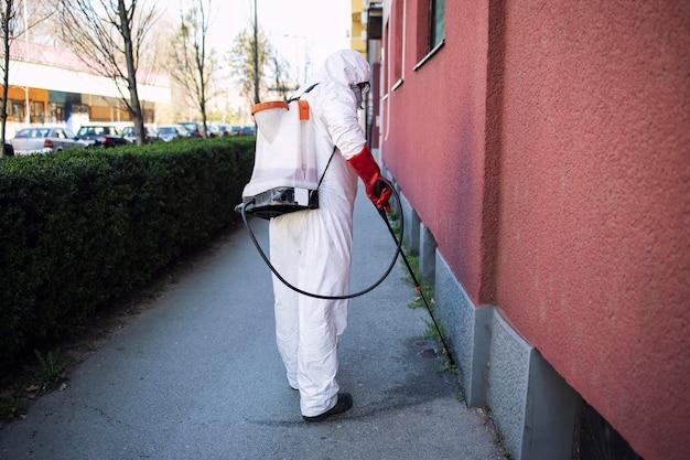 Irriconoscibile lavoratore in tuta di protezione chimica che spruzza disinfettante su superfici pubbliche.