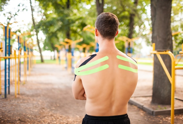 Irriconoscibile giovane culturista professionista caucasico con nastri kinesiologici neri e verdi su spalle muscolose nude in posa al campo sportivo.