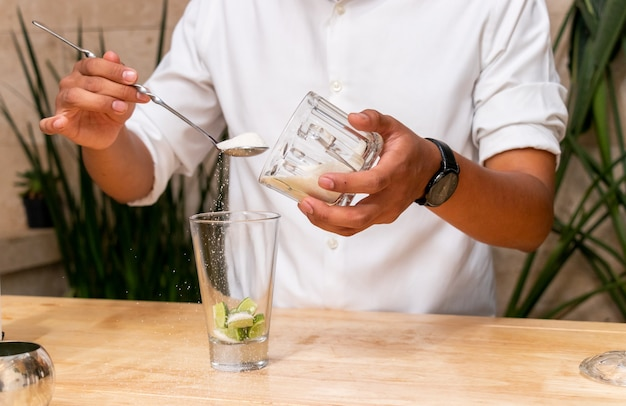 Un giovane irriconoscibile che prepara un drink in una ciotola di vetro con limoni e zucchero
