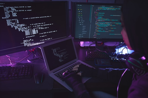 Giovane irriconoscibile circondato da più schermi di programmazione o hacking della sicurezza in camera oscura, copia dello spazio