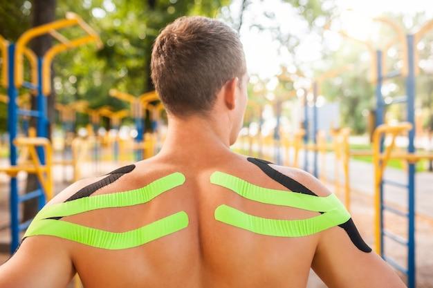 Irriconoscibile giovane bodybuilder professionista con nastri kinesiologici neri e verdi