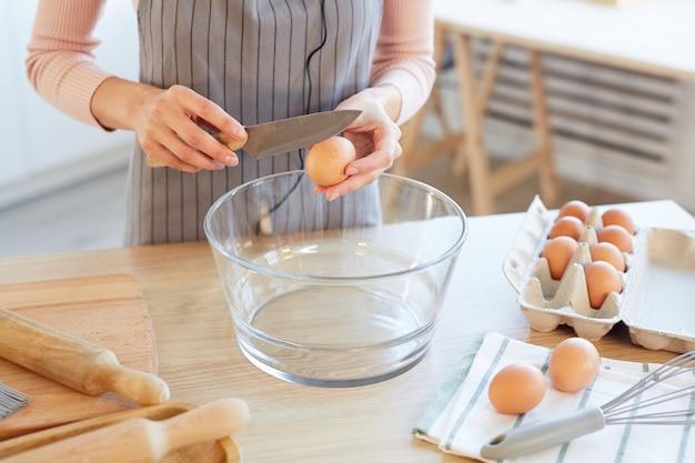 Irriconoscibile giovane donna cracking uovo nella ciotola di vetro per pasta da forno, colpo di alto angolo orizzontale