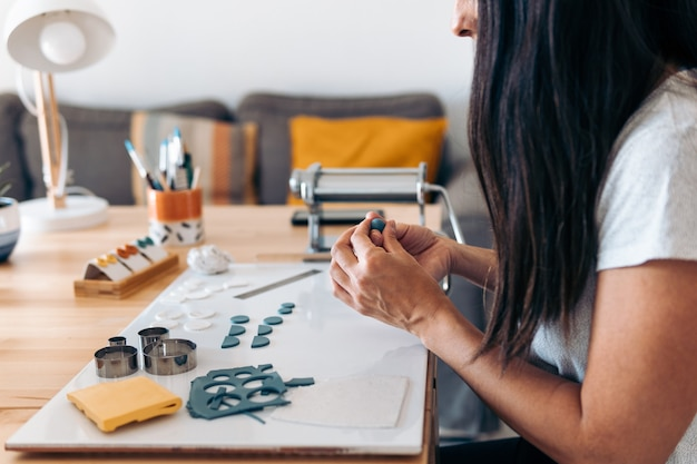 Artigiana non riconosciuta seduta a casa e che realizza gioielli fatti a mano con l'argilla.