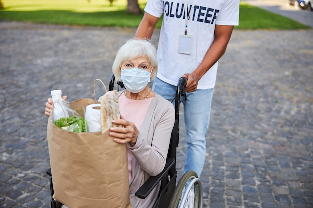 Volontario maschio non riconosciuto che spinge la sedia a rotelle di una donna anziana in maschera medica seduta con una borsa della spesa di carta