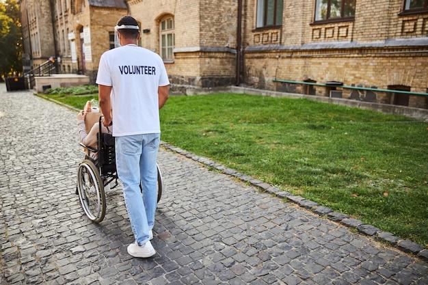Volontario maschio non riconosciuto che spinge la sedia a rotelle di una persona con disabilità vicino al vecchio edificio. banner del sito web