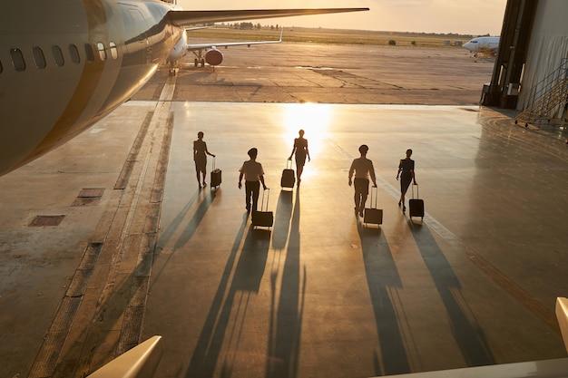 Piloti e hostess non riconosciuti che camminano vicino all'aereo passeggeri con le loro valigie