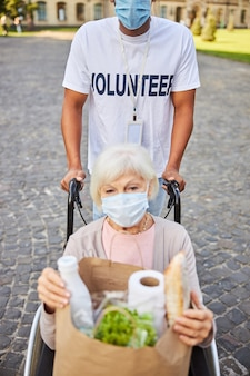 Volontario non riconosciuto con una maschera medica che spinge la sedia a rotelle di una donna anziana con una borsa della spesa