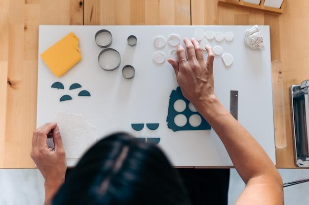 Donna non riconosciuta che crea gioielli fatti a mano colorati a casa con argilla e utilizza strumenti.