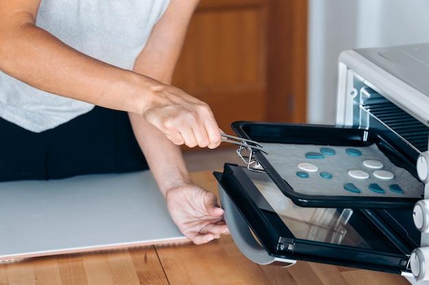 Donna non riconosciuta che crea gioielli fatti a mano usando il forno e lavorando da casa.