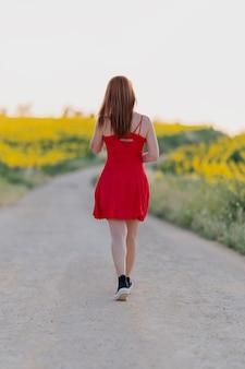 Donna non riconosciuta che indossa un abito rosso che cammina in un campo di girasoli e si gode il tramonto.