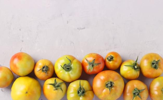 Pomodori acerbi su fondo di cemento grigio chiaro con posto per il testo, vista dall'alto
