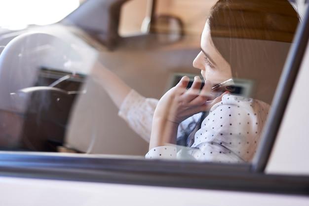 Guida non sicura giovane donna multirazziale che parla al telefono mentre guida una donna distratta alla guida