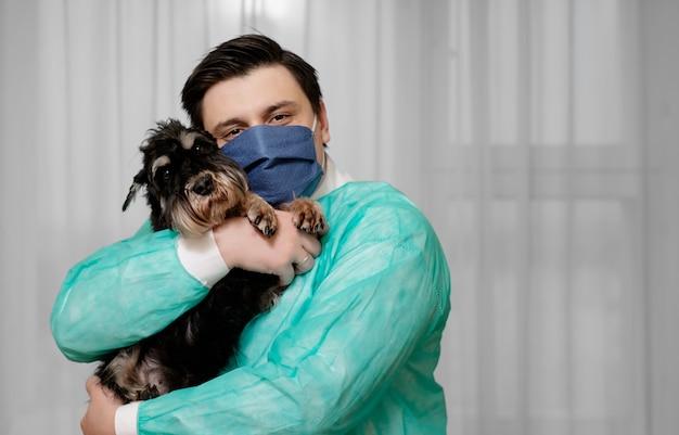 Condizioni non sanitarie, il medico tiene tra le mani un cane malato di coronavirus,