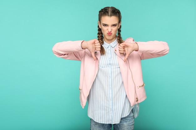 Ritratto di antipatia insoddisfatta di bella ragazza carina in piedi con trucco e acconciatura a codino marrone in giacca rosa camicia a righe azzurre. indoor, studio shot isolato su sfondo blu o verde.