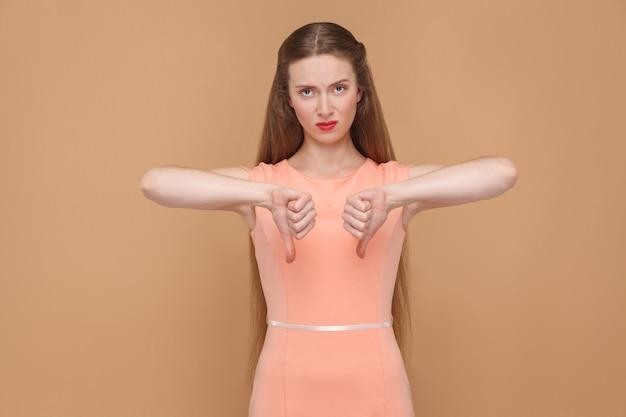 La donna insoddisfatta mostra il pollice verso il basso e guarda la telecamera. ritratto di una donna emotiva carina e bella con il trucco e i capelli lunghi in abito rosa, scatto in studio isolato su sfondo marrone chiaro o beige