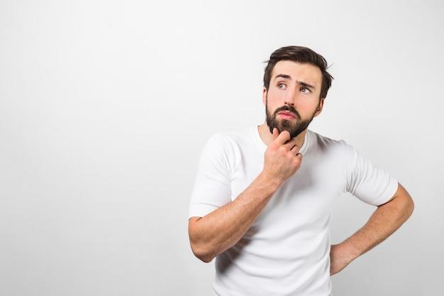 Un ragazzo rasato e riflessivo indossa camicia bianca e posa. sta tenendo il braccio destro vicino al mento e sta pensando. isolato sul muro bianco