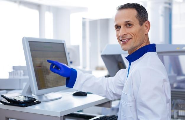 Progresso inarrestabile. ricercatore intelligente bello che tocca lo schermo del sensore di apparecchiature mediche all'avanguardia e sorride mentre guarda dritto