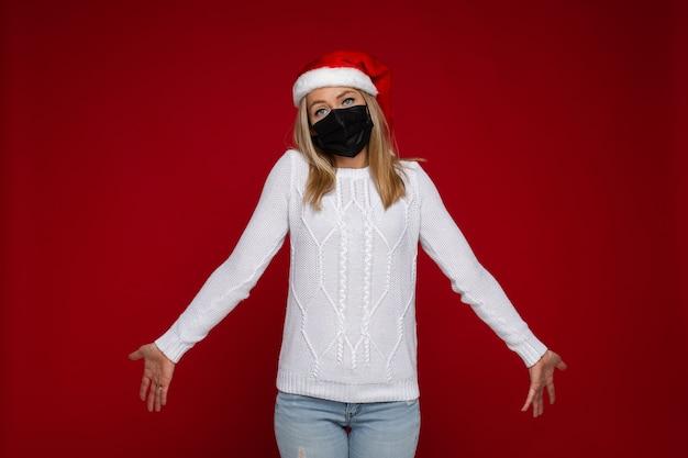 Donna caucasica bionda incerta in maglione bianco, jeans, cappello rosso della santa e maschera facciale nera che scrolla le spalle nelle spalle nel dubbio.