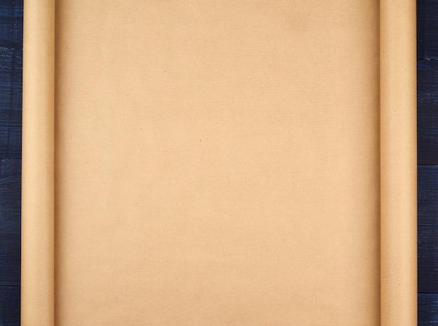 Rotolo non distorto della carta marrone del mestiere su un fondo di legno blu, spazio vuoto