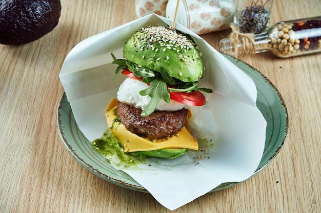 Un insolito hamburger fatto con metà dell'avocado, come panini con hamburger di manzo, pomodori, formaggio, uovo in camicia e rucola con pesto. visualizza. cibo sano e verde.
