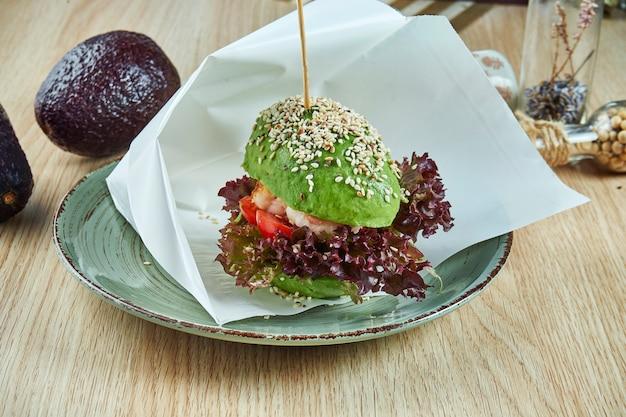 Un insolito hamburger fatto con metà di avocado, come panini con pomodoro e lattuga, gamberi. visualizza. cibo sano e verde.