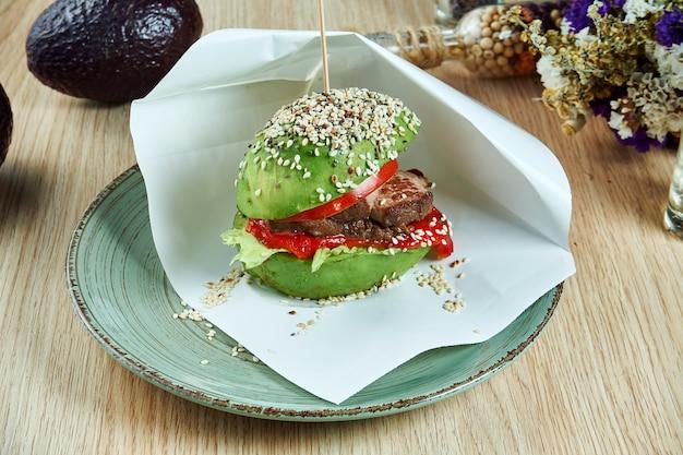 Hamburger insolito a base di metà di avocado con formaggio, bistecca di manzo e pomodoro. cibo di strada gustoso e salutare.