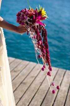 Un insolito bouquet da sposa allungato nelle mani della sposa.