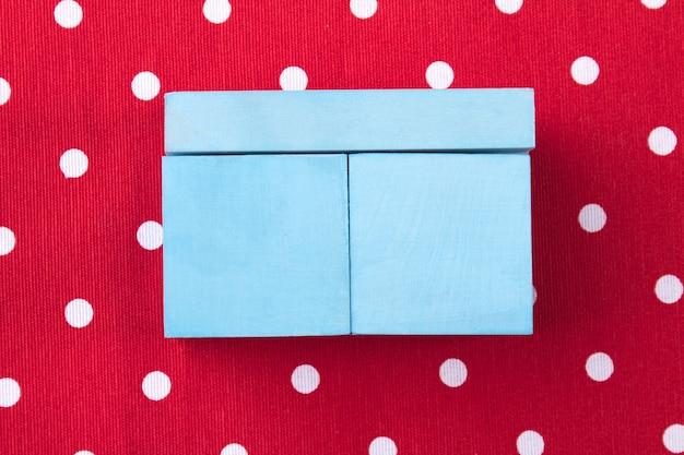Scatola regalo insolita piccola scatola blu su sfondo rosso punteggiato