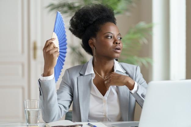 Un'impiegata d'ufficio africana indisposta subisce un colpo di calore sul posto di lavoro senza aria condizionata