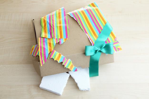 Confezione regalo da scartare e aperta su fondo in legno
