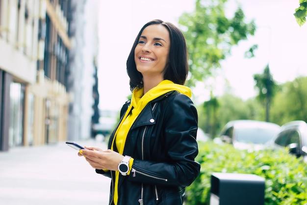 Tecnologie aggiornate! giovane donna, felice di possedere le sue tecnologie aggiornate, come smartphone e smartwatch.