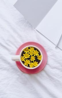 Ðup con fiori gialli all'interno, su un letto bianco con blocco note e penna.