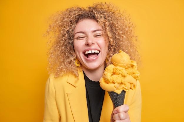 La giovane donna allegra ottimista ha i capelli folti ricci sorride ampiamente mentre sente che qualcosa di divertente si tratta con un gustoso gelato freddo vestito elegantemente posa contro il muro giallo.