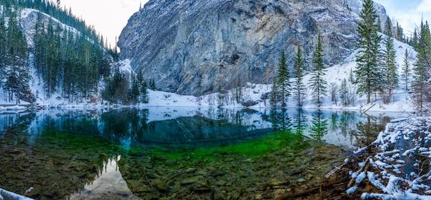 Laghi dell'alto grassi nella stagione invernale. il riflesso della superficie del lago come uno specchio. canmore, alberta, canada.