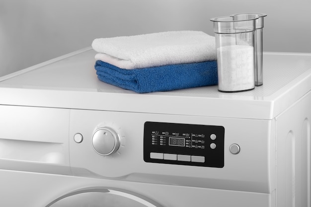 La parte superiore della lavatrice con un asciugamano e un contenitore con detersivo