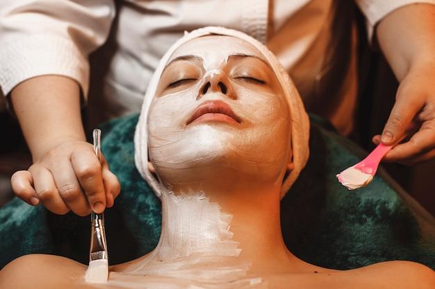 Vista superiore di una donna affascinante che si appoggia su un letto spa con gli occhi chiusi con una maschera bianca sul viso e sul collo.
