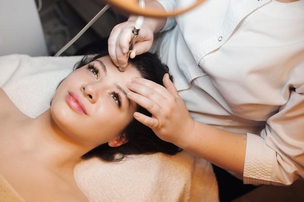Vista superiore di una bella donna con procedure di lifting facciale sul viso appoggiato su un letto spa con gli occhi aperti.