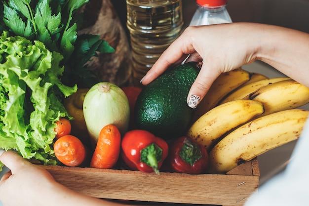 Foto vista dall'alto di una scatola piena e frutta verdura acquistata per l'accaparramento in quarantena