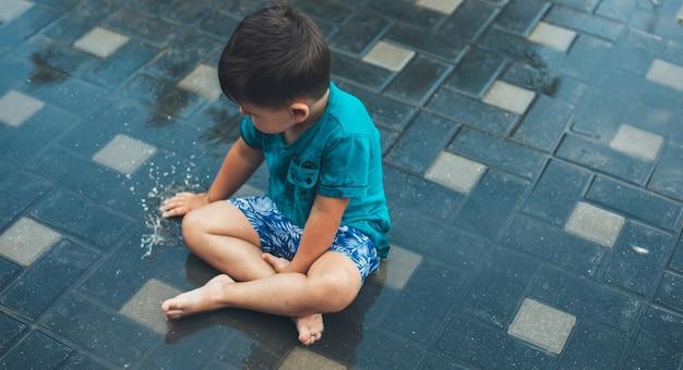 Foto di vista superiore di un ragazzo caucasico che gioca con l'acqua sul terreno dopo una pioggia