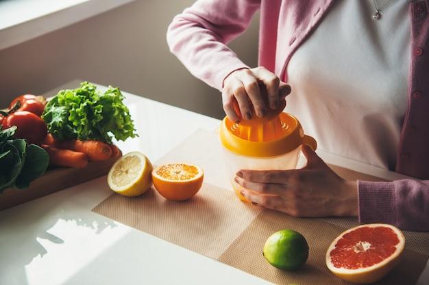 Foto di vista superiore di una donna caucasica che spreme il succo fresco dalla frutta usando uno spremiagrumi