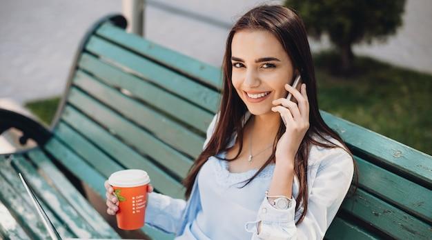 Foto vista dall'alto di un'affascinante signora che parla al telefono e beve un caffè seduto sulla panchina con un laptop