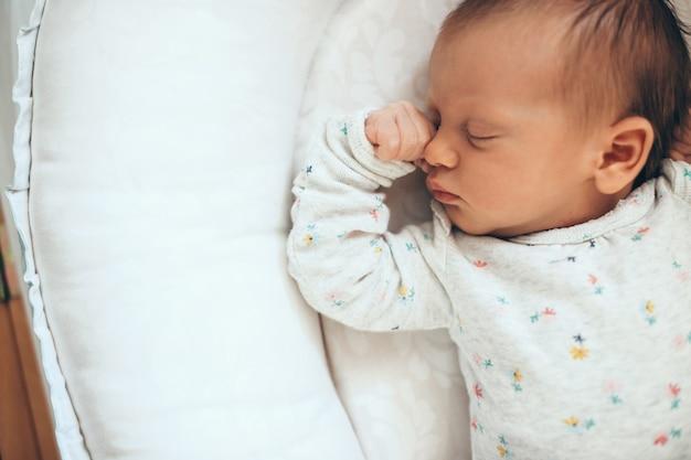 Foto di vista superiore di un neonato che dorme in cassaforte su un letto bianco